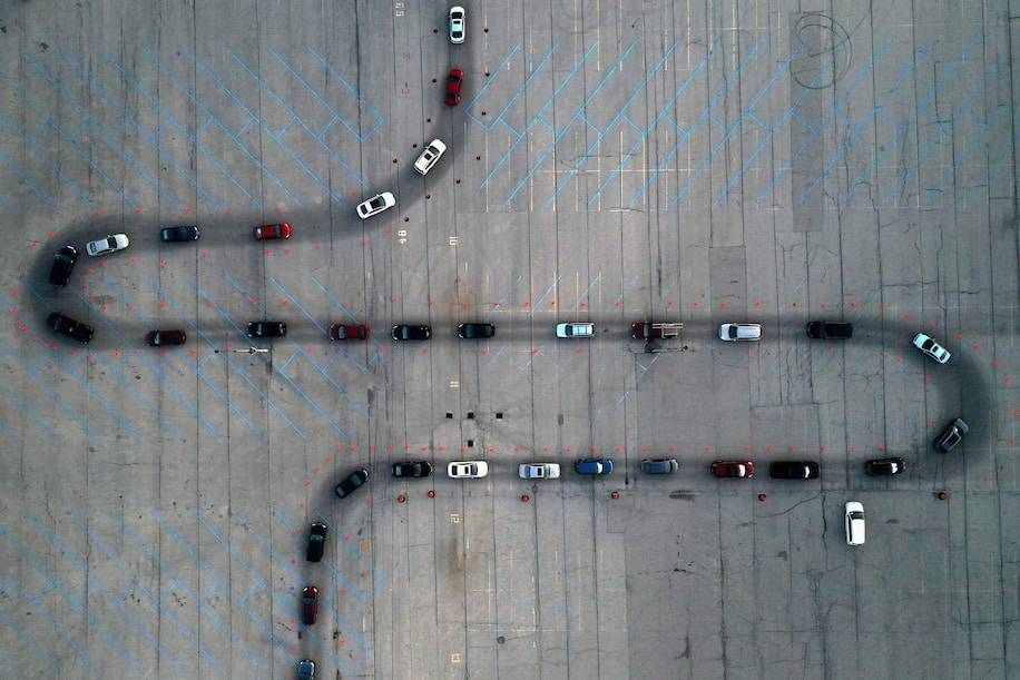 People wait in their vehicles on Sunday at a drive-through coronavirus testing site in Milwaukee. (Bing Guan/Reuters)