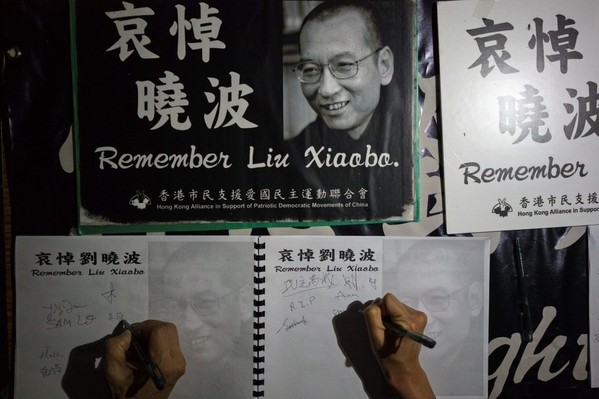 People sign their names at a memorial event for late Chinese Nobel laureate Liu Xiaobo in Hong Kong on July 19. (Aaron Tam/Agence France-Presse via Getty Images)