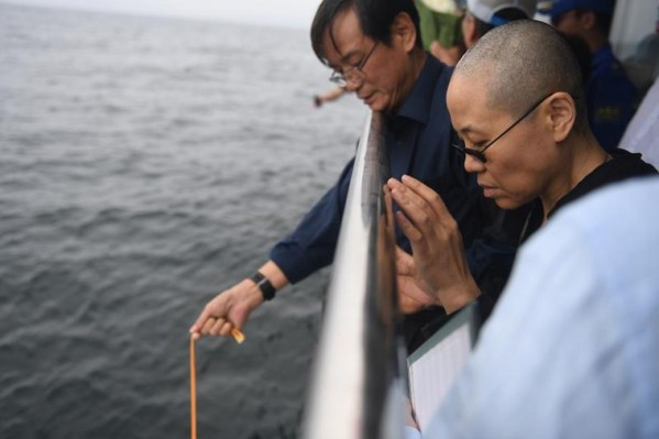 Liu Xiaobo's wife, Liu Xia, prays as his ashes are buried at sea off the coast of Dalian, China, on July 15. (Agence France-Presse/Shenyang Municipal Information Office)