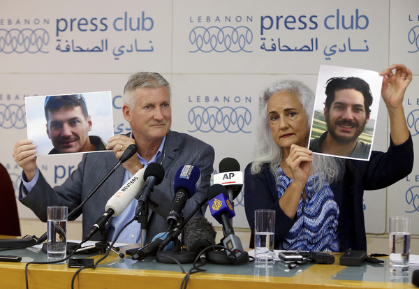 Marc and Debra Tice, the parents of Austin Tice,&amp;nbsp;hold up photos of him during a press conference Beirut on July 20. (Bilal Hussein/Associated Press)</p>