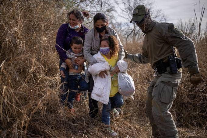 Asylum-seeking migrants who crossed the Rio Grande into the United States from Mexico weep as a Texas state trooper takes them out of thick brush, in Penitas, Tex., on Tuesday. (Adrees Latif/Reuters)