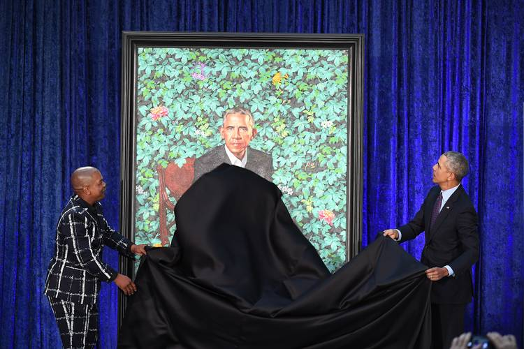 Artist Kehinde Wiley and Barack Obama take a cloth from Obama's presidential portrait at the Smithsonian National Portrait Gallery. (Matt McClain/The Washington Post)