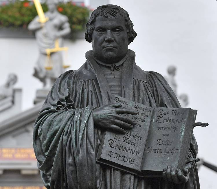 A statue of Martin Luther holding his translation of the New Testament into German sits in front of the city hall in Wittenberg, Germany. (Hendrik Schmidt/AFP/Getty Images)
