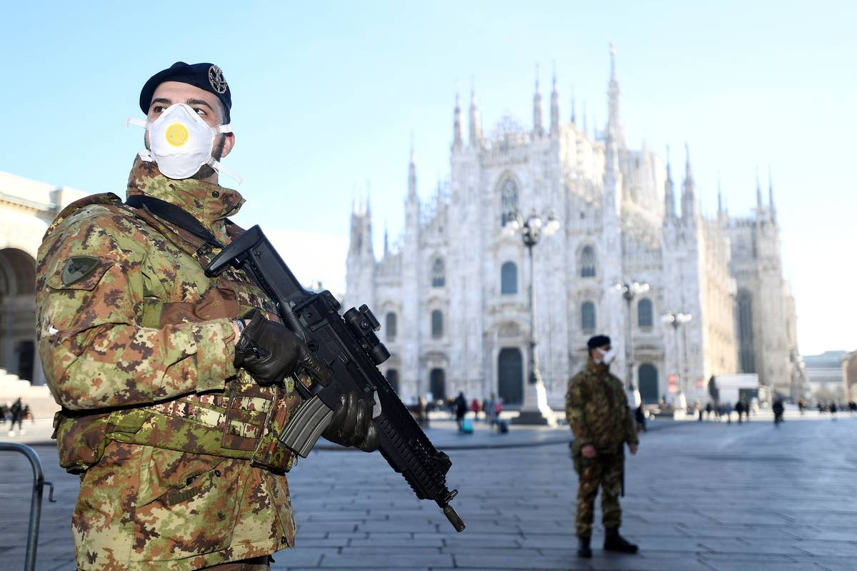 Military officers wearing face masks stand outside the Duomo cathedral, closed by authorities due to a coronavirus outbreak, in Milan on Feb. 24. (Flavio Lo Scalzo/Reuters)