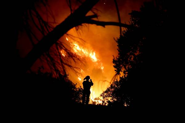 A firefighter takes a cell phone picture during a wildfire Saturday. (AP Photo/Chris Carlson)