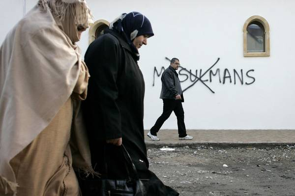 Muslim residents of Saint-Etienne, France, walk past racial slurs painted on the walls of a mosque there in 2010.&amp;nbsp;(Laurent Cipriani/Associated Press)</p>
