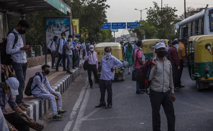 Commuters wait for transport Tuesday in Delhi. India is relaxing its lockdown restrictions. (Yawar Nazir/Getty Images)