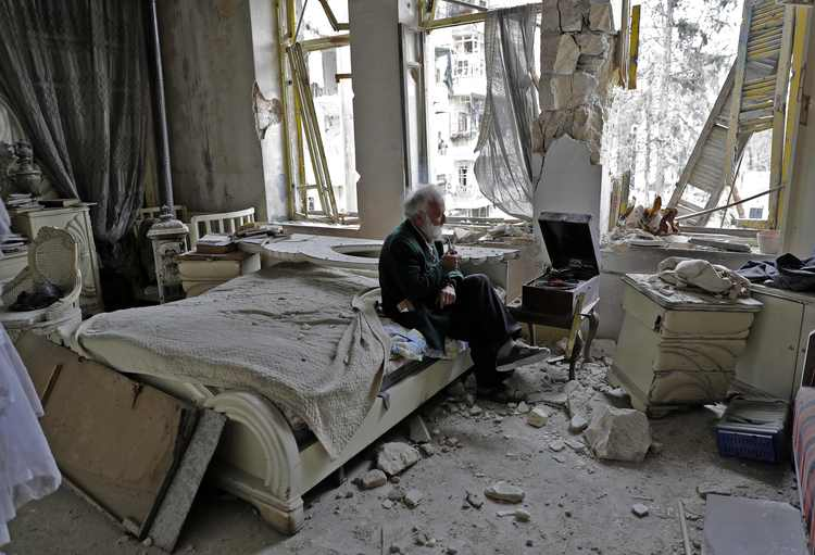 This photo of 70-year-old Mohammad Mohiedine Anis, smoking a pipe in his gutted Aleppo apartment, has gone viral. (AFP/Joseph Eid)/p