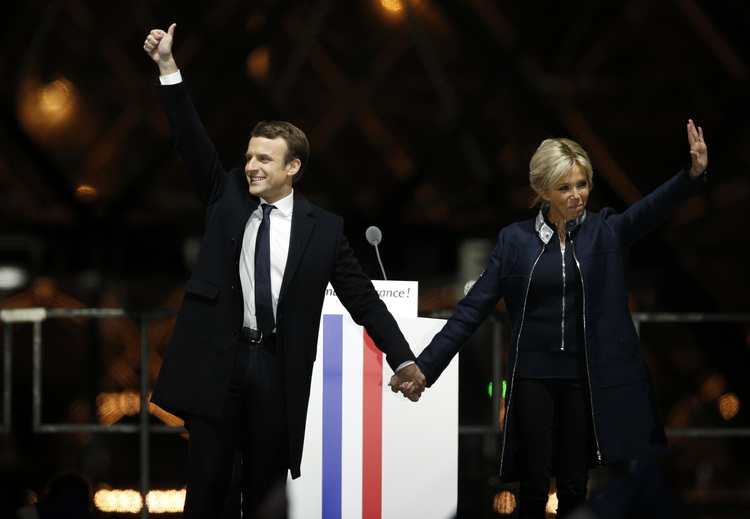 Emmanuel Macron holds hands with his wife Brigitte during a victory celebration outside the Louvre museum. (AP/Thibault Camus)/p