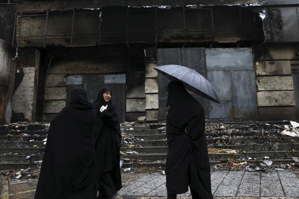 Women walk past a building damaged during recent protests, in Shahriar, Iran, on Nov. 20. (Vahid Salemi/AP)
