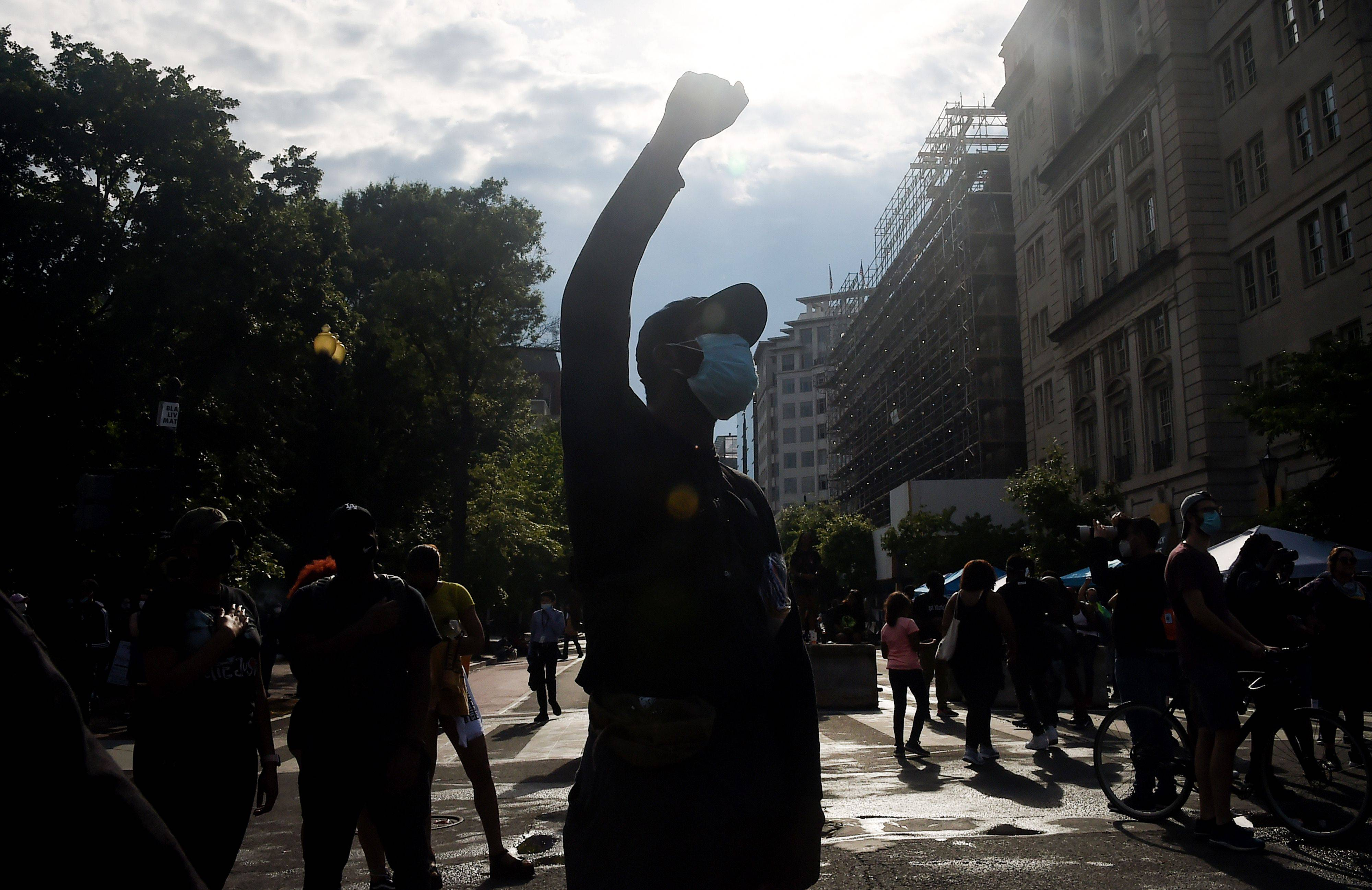 A demonstrator raises his fist near the White House. (Olivier Douliery/AFP via Getty Images)