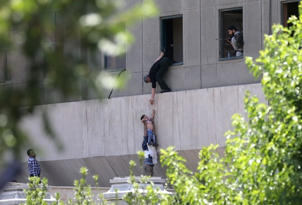 Iranian policemen evacuate a child from the parliament building in Tehran on June 7. (Omid Vahabzadeh/Agence France-Presse via Getty Images)