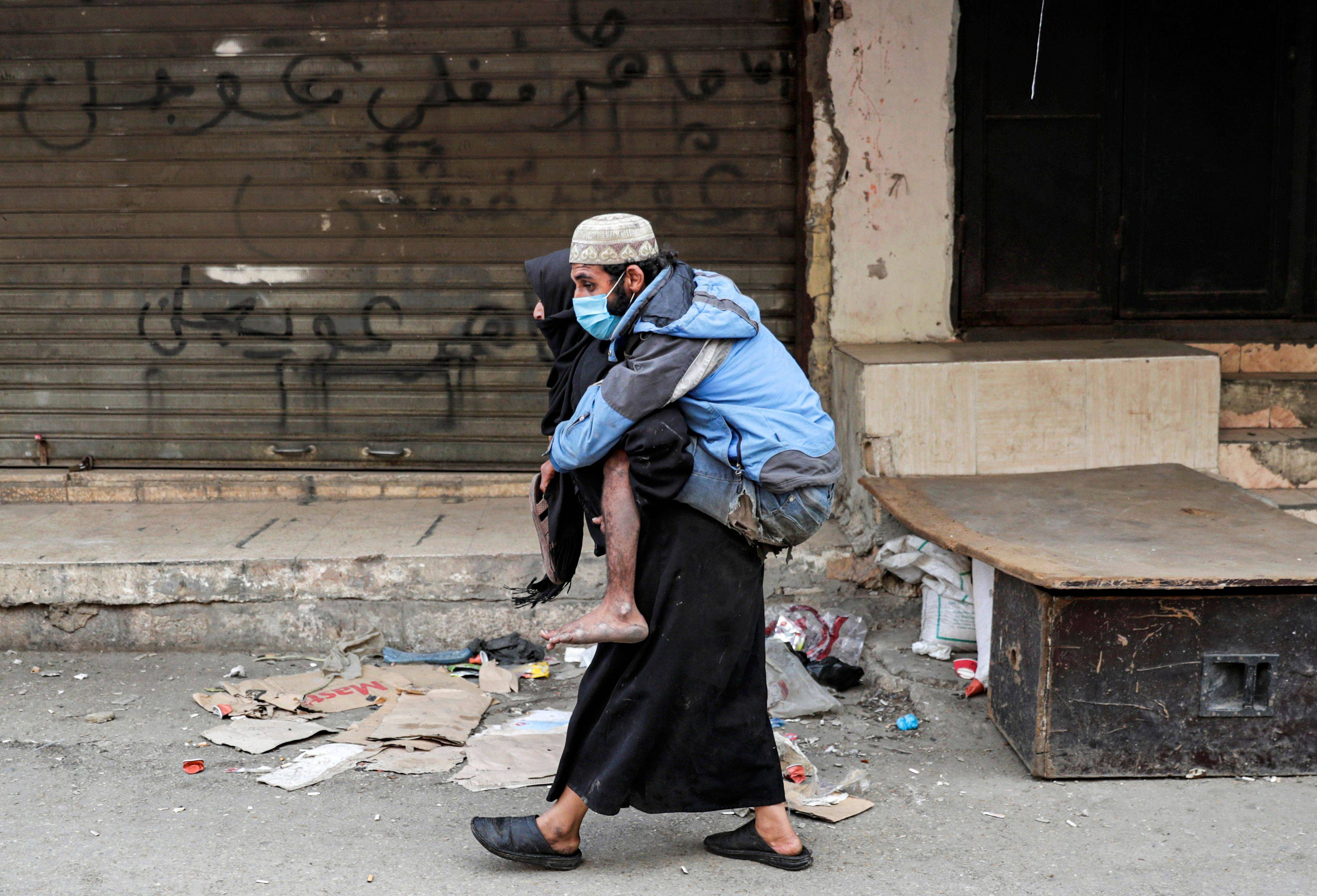 A woman carries a man wearing a protective face mask in the market of the Palestinian refugee camp of Sabra south of Beirut on March 22. (Anwar Amro/AFP/Getty Images)
