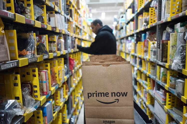 A clerk reaches to a shelf to pick an item for a customer order at the Amazon Prime warehouse in New York. (Mark Lennihan/AP)