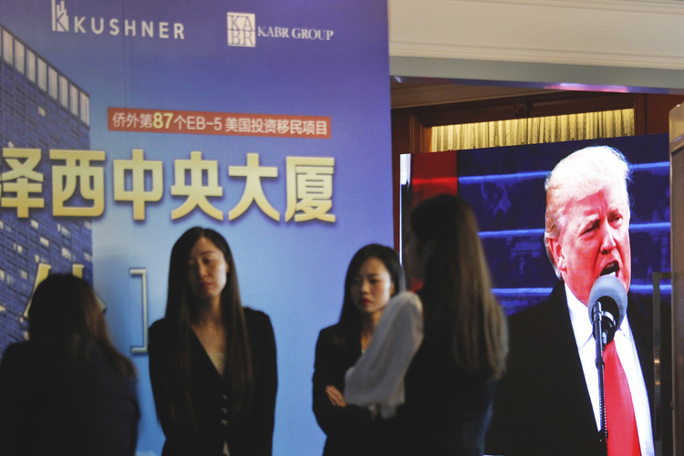 A projector shows Trump footage onscreen, as workers wait at an event promoting EB-5 in China. (AP)/p
