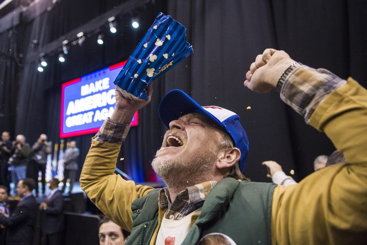 Jake Buird throws popcorn and shouts in celebration after seeing Trump up close. (Photo by Jabin Botsford/The Washington Post)