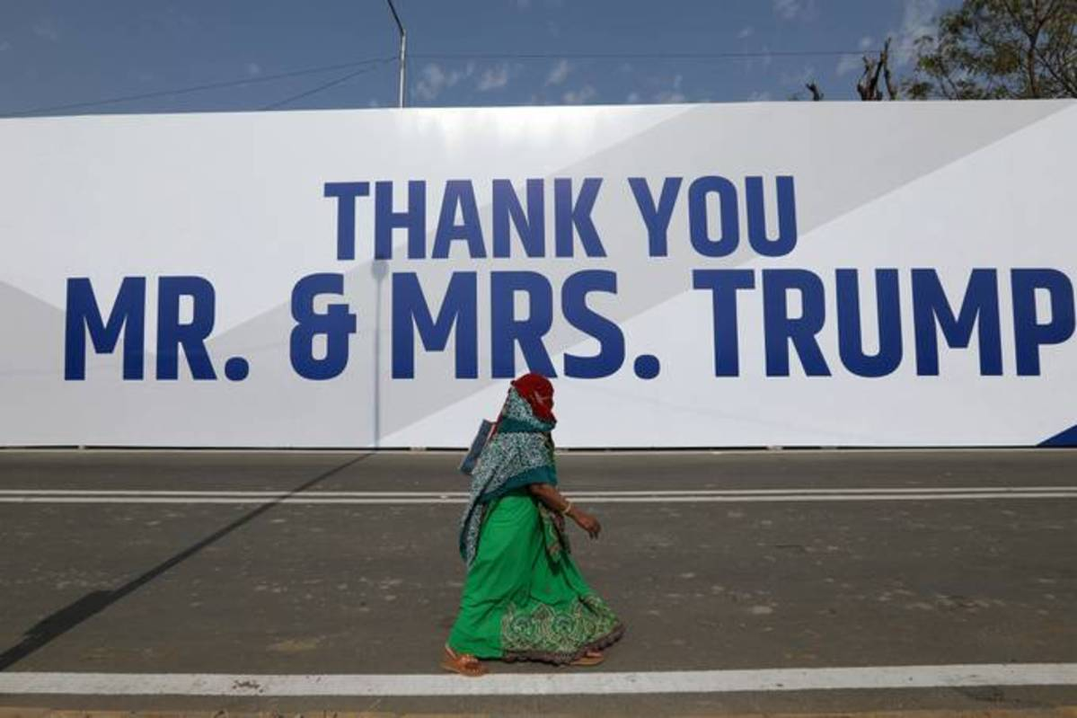 A woman walks past hoardings featuring the words 'Thank You Mr. And Mrs. Trump' on a route to Motera Stadium in Ahmedabad, India, on Feb. 23. (T. Narayan/Bloomberg)