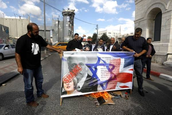 Palestinian protesters burn a banner of Balfour, British and Israeli flags during a protest in the city of Bethlehem on Nov. 1. (Abed Al Hashlamoun/European Pressphoto Agency-EFE)