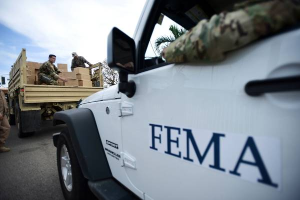 In this file photo, Department of Homeland Security personnel deliver supplies to Santa Ana community residents in the aftermath of Hurricane Maria in Guayama, Puerto Rico. (AP Photo/Carlos Giusti, File)