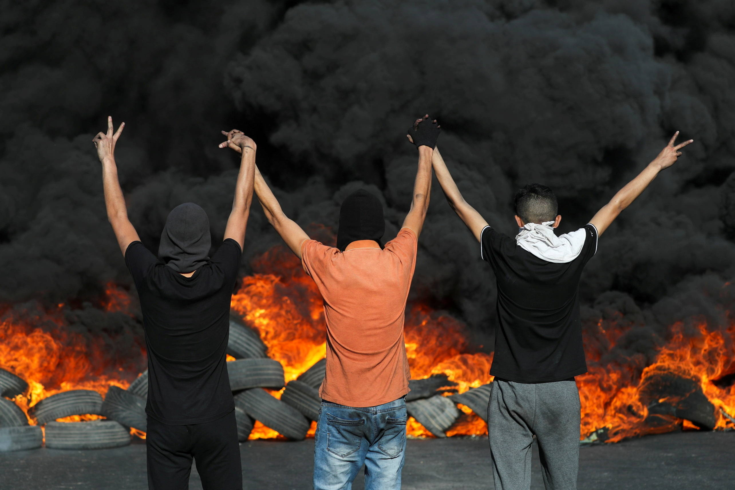 Palestinian demonstrators look at burning tires during a protest in the Israeli-occupied West Bank. (Reuters/Ammar Awad)