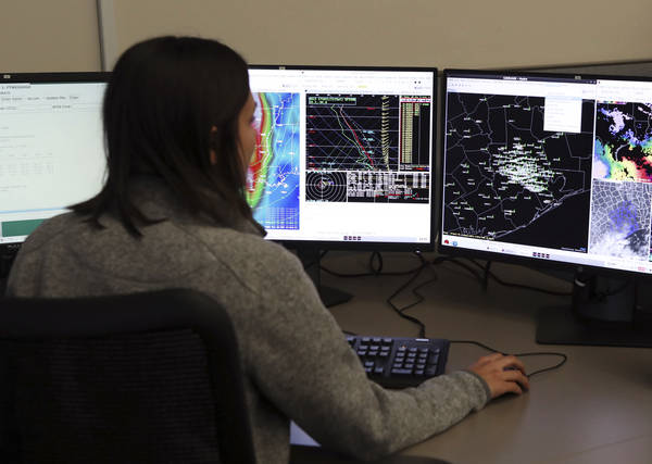 A meteorologist works at her desk in the National Weather Service office in Dickinson, Tex. Many of the employees had to sleep in the office during Hurricane Harvey as they could not drive to their houses. (Kelsey Walling/The Galveston County Daily News via AP)
