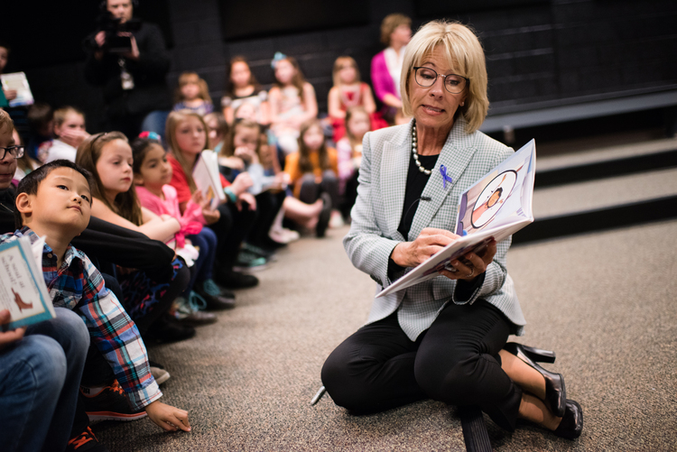 Betsy DeVos reads a story about military mothers to a group of students. (Sarah L. Voisin/The Washington Post)/p