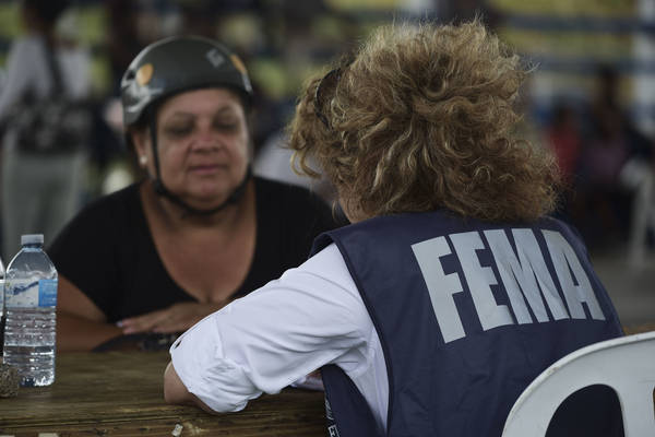 A resident meets with a FEMA representative to file forms for federal aid in the aftermath of Hurricane Maria at the Jose de Diego Elementary School in Las Piedras, Puerto Rico. (AP Photo/Carlos Giusti)