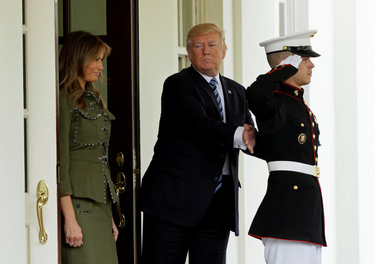 Trump pats a Marine on the back yesterday after he tended the limo doors for the departure of Argentine President Mauricio Macri from the White House. (Kevin Lamarque/Reuters)/p