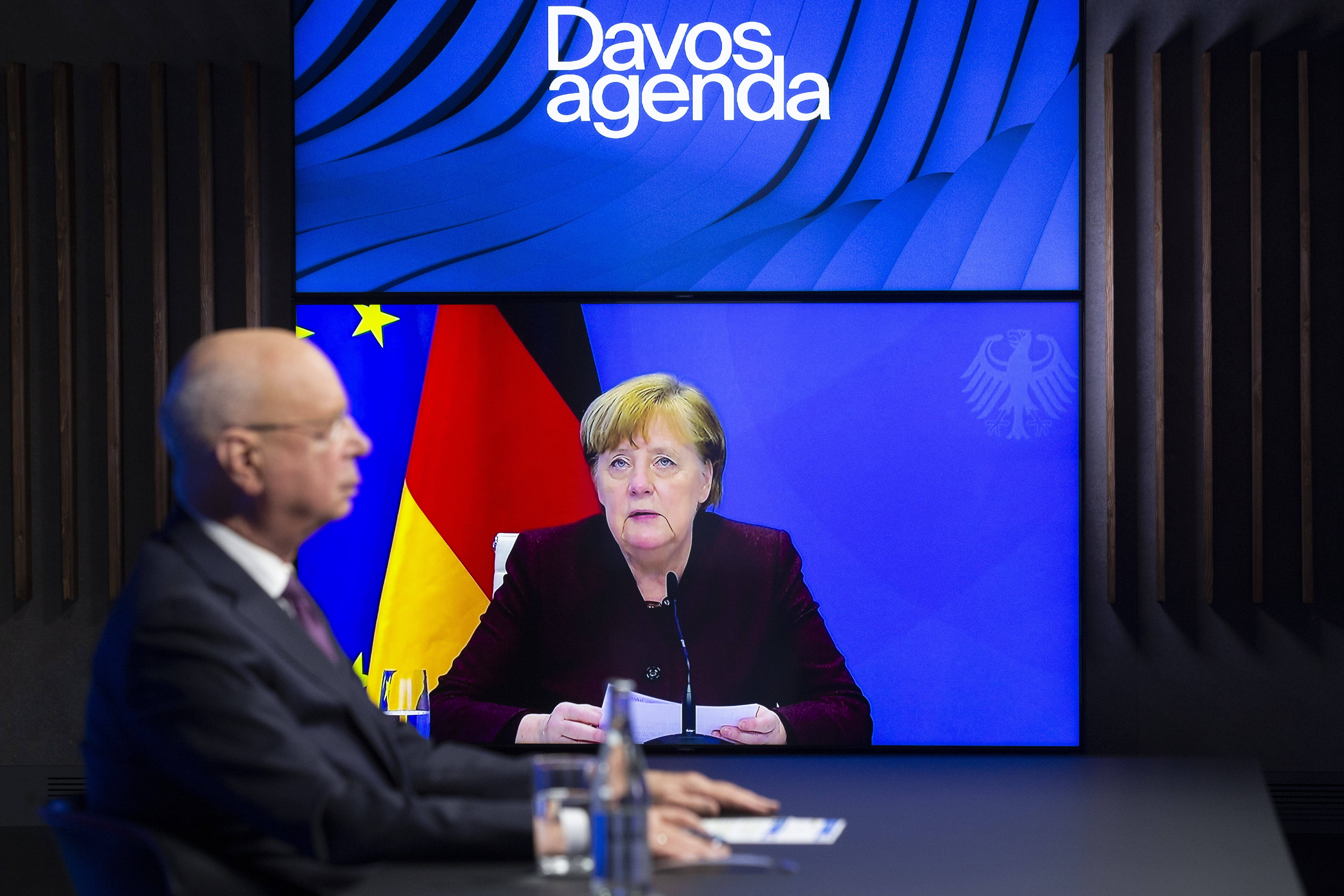 Klaus Schwab, left, the founder and executive chairman of the World Economic Forum, listens to German Chancellor Angela Merkel, shown on a video screen, as part of the group's annual conference in Davos, Switzerland, on Jan. 26. (Salvatore Di Nolfi/Keystone/AP)
