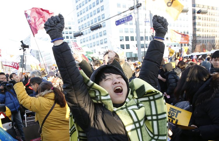 South Koreans cheer after lawmakers approved the impeachment of President Park in front of the National Assembly in Seoul. (Jeon Heon-Kyun/EPA)</p>