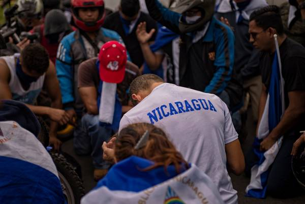 Young anti-Ortega rebels pray on July 15 in Managua, Nicaragua. (Juan Carlos/The Washington Post)</p>