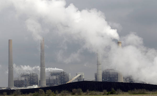 Exhaust rises from smokestacks in front of piles of coal in Thompsons, Tex. (AP Photo/David J. Phillip, File)