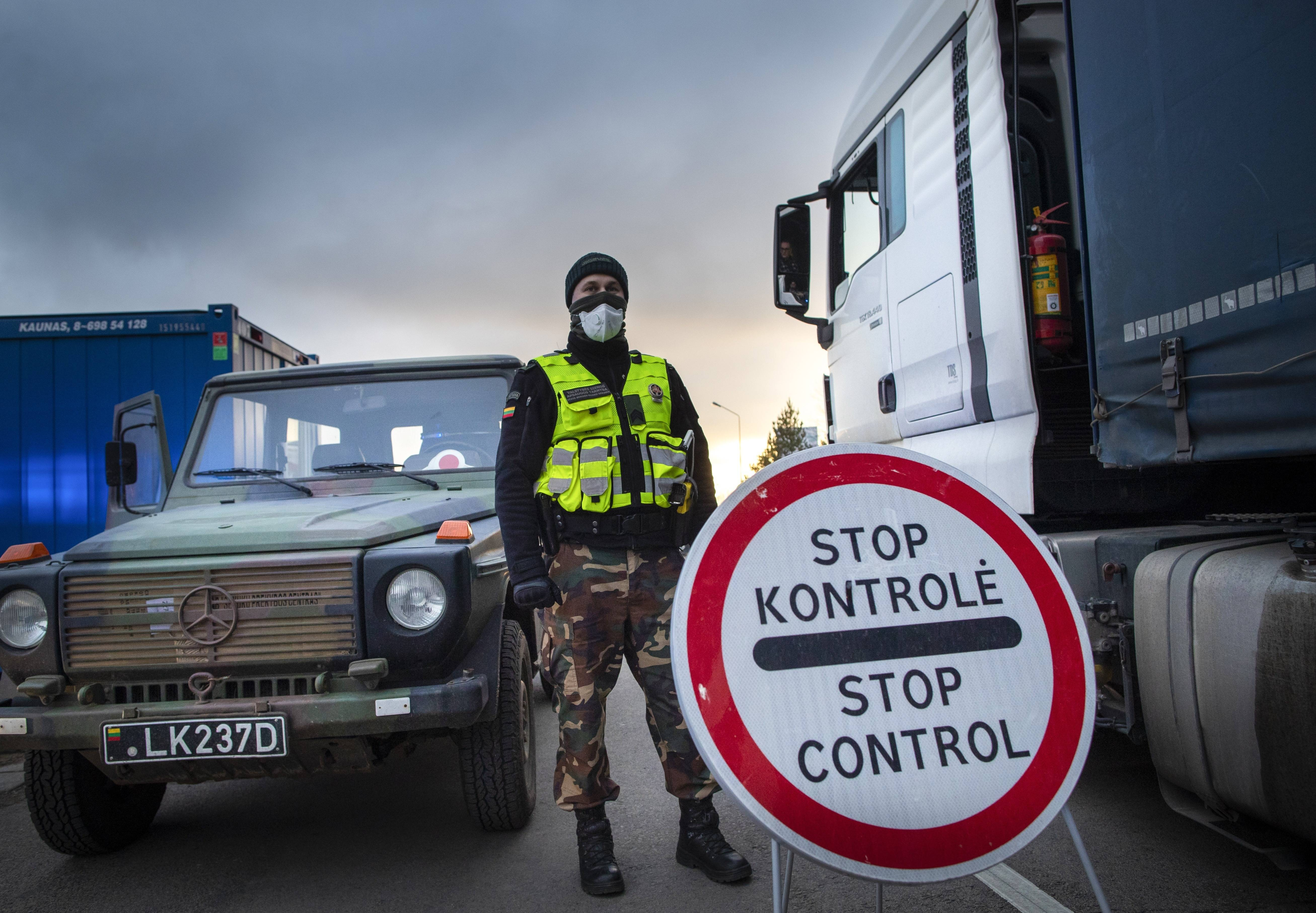 A Lithuanian border guard stands next to trucks stuck in traffic near the border with Poland. (Mindaugas Kulbis/AP)