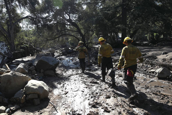 A Los Angeles County search and rescue team walks through a neighborhood that was destroyed by a mudslide on Jan. 11 in Montecito, Calif. (Photo by Justin Sullivan/Getty Images)