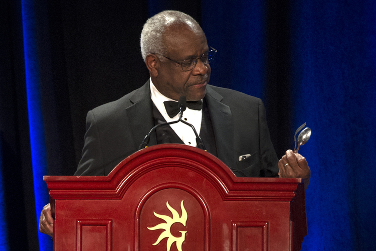 Clarence Thomas comments on a spoon and fork he found on the podium while addressing the Federalist Society&#39;s National Lawyers Convention dinner at National Harbor last night. (Cliff Owen/AP)</p>