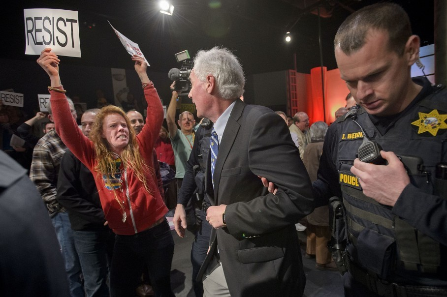 Local police escort Republican Rep. Tom McClintock from a town hall meeting  in Roseville, Calif. last Saturday. McClintock on Saturday faced a rowdy  crowd ...