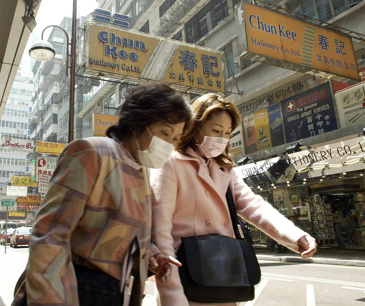 Two women wear masks in Hong Kong on March 25, 2003. (Peter Parks/AFP/Getty Images)