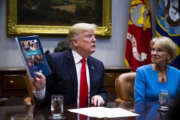 President Trump holds up the Federal Commission on School Safety report while Betsy DeVos listens during a roundtable discussion in the Roosevelt Room at the White House in December. (Al Drago/Bloomberg)