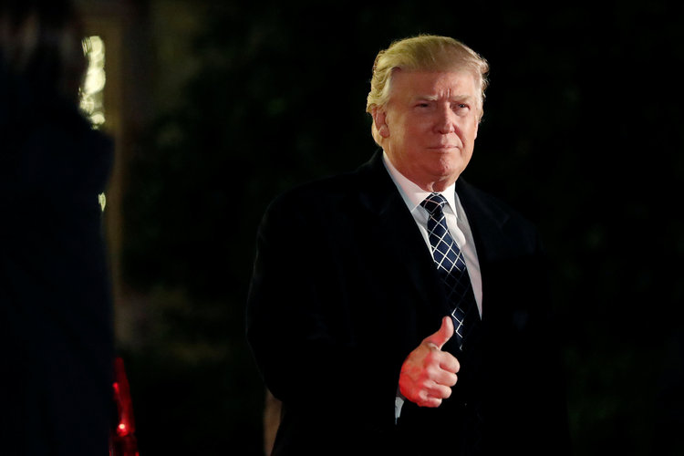 Trump gives a thumbs up as he arrives at a costume party at the home of hedge fund billionaire and major campaign donor Robert Mercer in New York last December. (Mark Kauzlarich/Reuters)/p