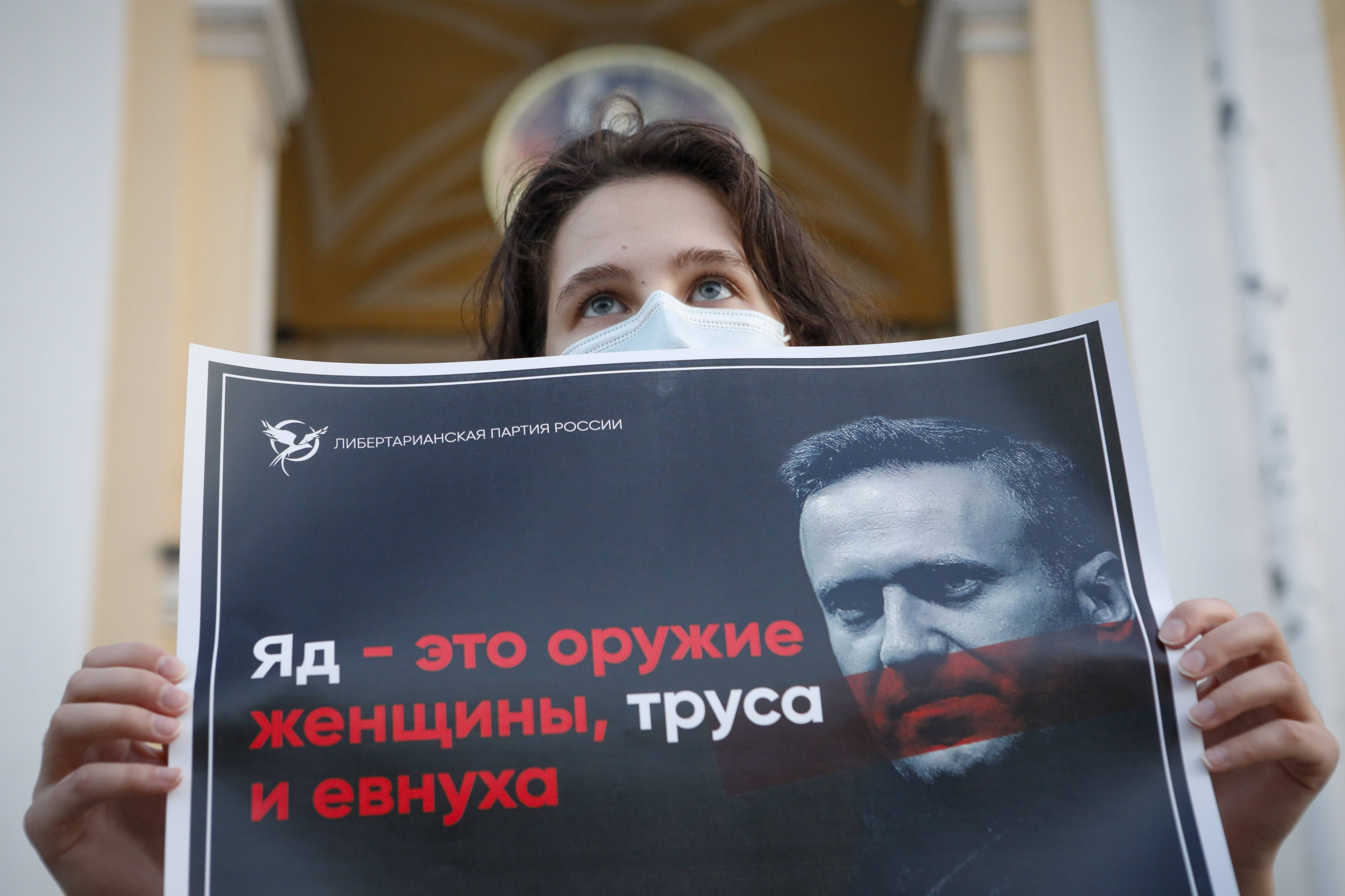 """A protester in St. Petersburg last week holds a poster that reads """"poison is the weapon of a woman, a coward and a eunuch!"""" (Elena Ignatyeva/AP)"""