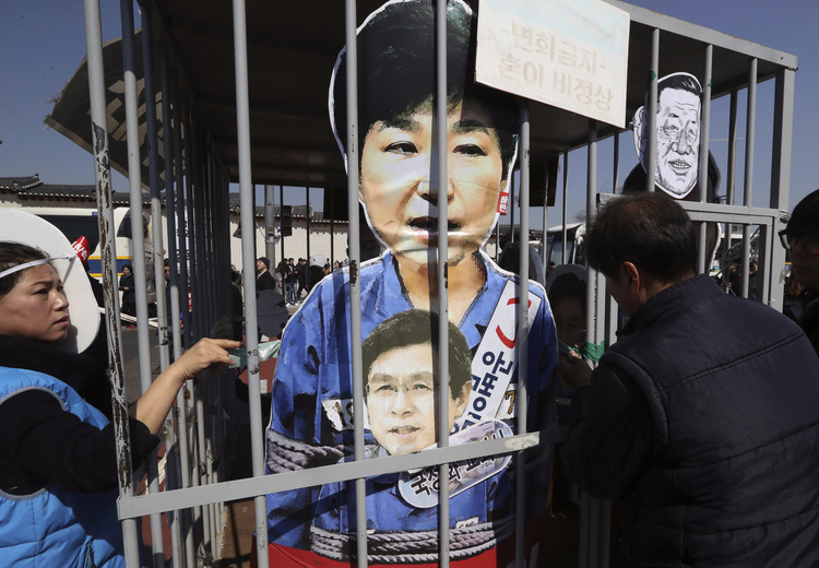 Protesters look at cutouts of impeached President Park and acting leader Hwang Kyo-ahn in a mock jail. (Lee Jin-man/AP)/p