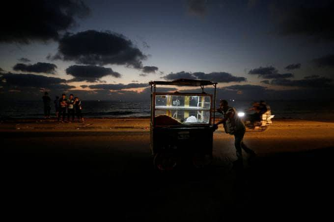 A Palestinian vendor sells sweets during a power outage on a beach in the Gaza Strip on Aug. 18. (Mohammed Salem/Reuters)