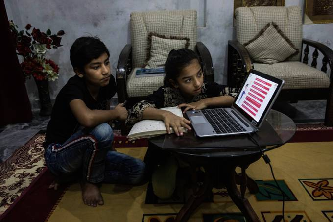 Ayesha and her cousin Jamal both 13 do their homework following the classes on PTV (Pakistan Television) online program called teleschool in Islamabad. (Sarah Caron for The Washington Post)