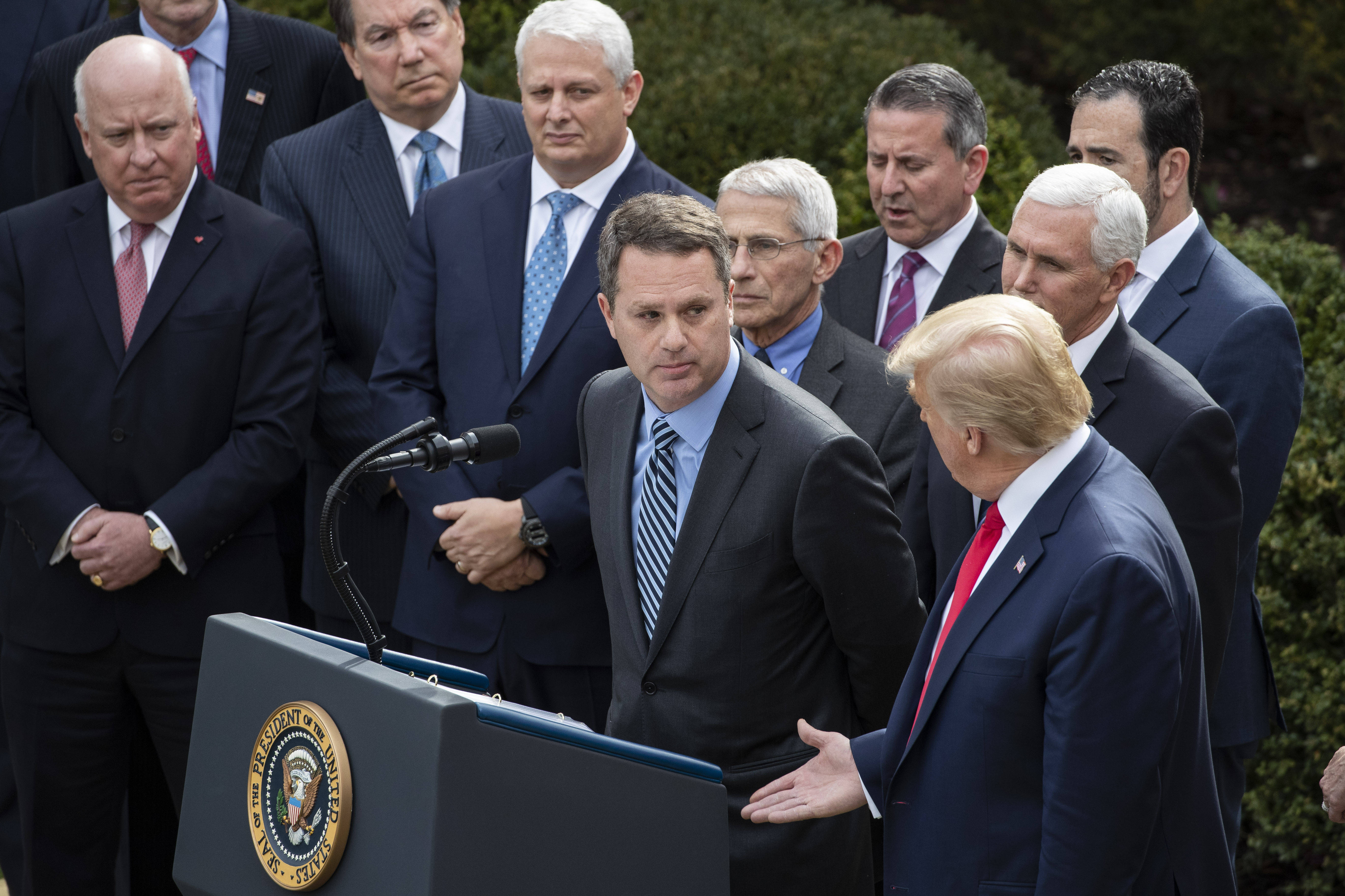 President Trump offers a handshake to the CEO of Walmart, Doug McMillon, during a coronavirus briefing March 13 as his administration urges Americans not to shake hands, among other social distancing measures. (Alex Brandon/AP)